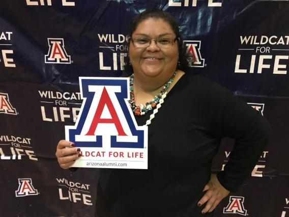 a person smiling at the camera holding a UA sign that says Wildcat for Life
