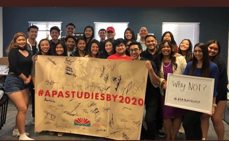 Students hold up a signed banner that reads APA Studies By 2020